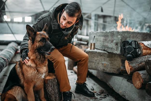 Сталкер, солдат постапокалипсиса кормит собаку