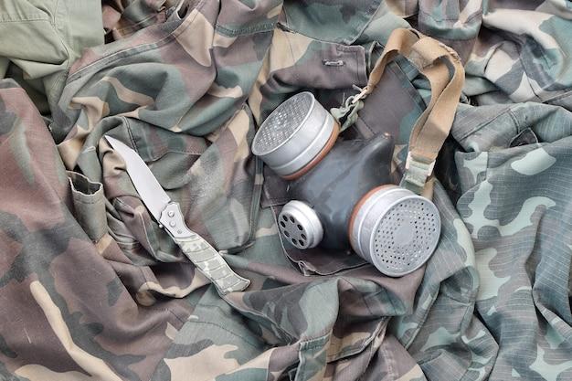Советский противогаз солдат-сталкеров лежит с ножом на зеленой камуфляжной куртке цвета хаки. набор предметов для выживших после апокалипсиса