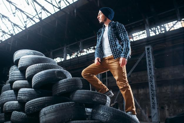 Stalker, traveler climbs a mountain of tires