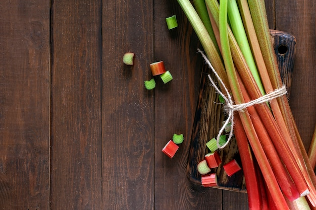 Stalks of fresh rhubarb on a wooden background with copy space.
