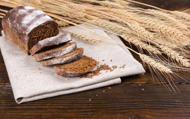 어두운 나무 테이블 위에 갈색 천으로 조각이있는 맛있는 호밀 빵 한 덩어리 옆에 말린 통밀 줄기와 곡물의 줄기