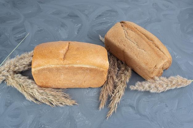 Gambi di erba piuma secca e pagnotte di pane si raggruppano insieme sul tavolo di marmo.