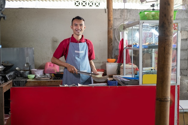 The stall waiter stands holding tongs while preparing the side dishes ordered by the customer at the shop