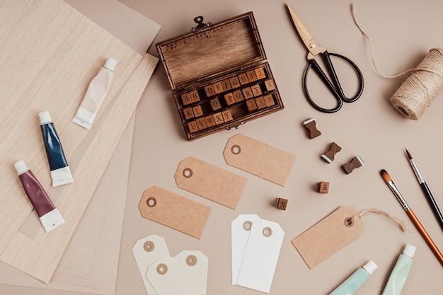 Stamp alphabet, paint, brushes, scissors and gift tags over beige background. craft, diy, hobby idea. flat lay, top view