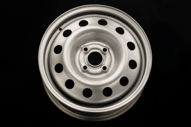 Stamped steel wheel for car, new grey on black background.
