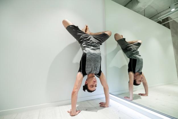 壁の近くに立ってください。灰色のショートパンツとtシャツを着た黒髪の男が壁と鏡の近くに立っている