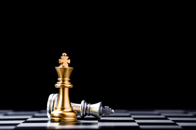 ゴールデンキングチェスとチェス盤に落ちたシルバーキングチェスのスタンド。ビジネス競争とマーケティング戦略計画コンセプトの勝者。