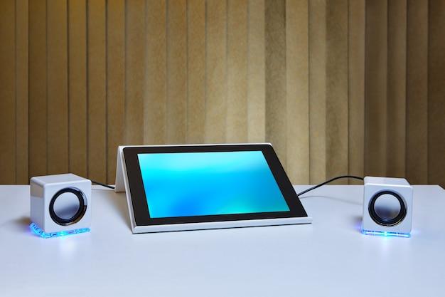 水色のディスプレイ画面と2つのミニチュアスピーカーを備えたタブレットpcのスタンド。
