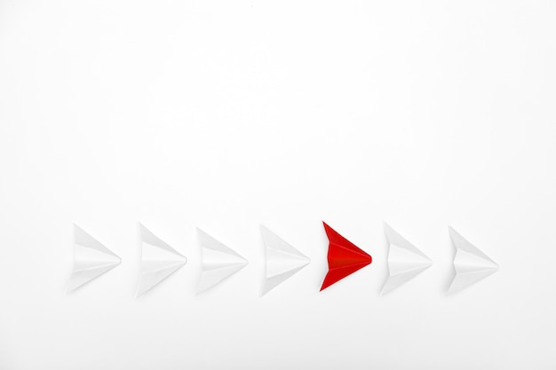 Stand out concept. red paper airplane standing out from line of white