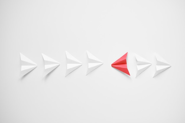 Stand out concept. red paper airplane standing out from line of whites and thrying to be against all.