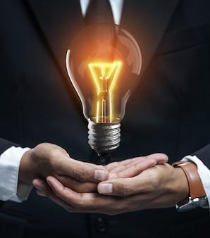 Выделиться концепция идеи с светящейся лампочкой в руке бизнесмена
