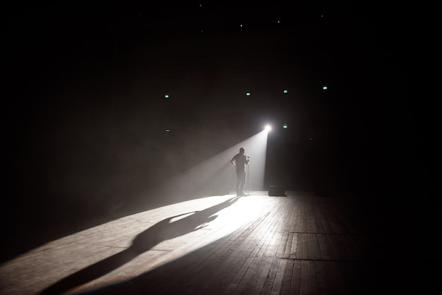 Stand up comedian on stage in the beam of light.