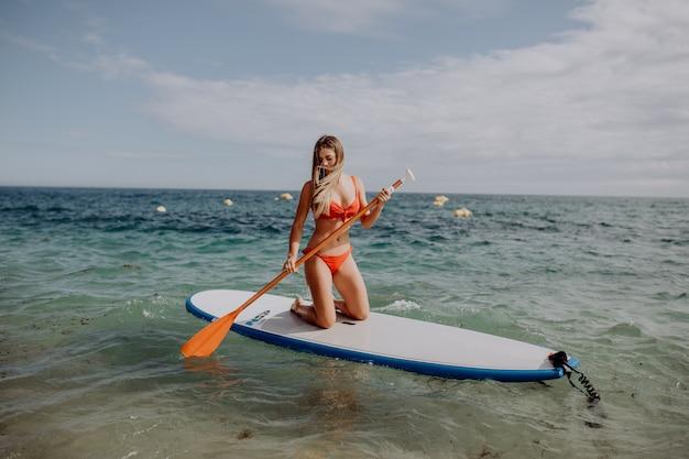 スタンドアップパドルボードの女性がsupでパドルボーディングをし、水中でパドルボードを楽しんでいます。