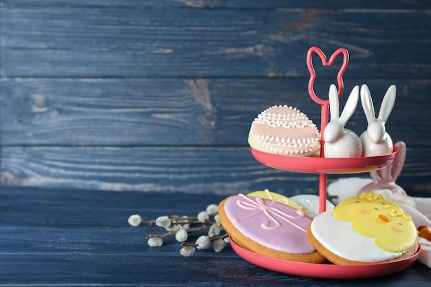 Подставка с красивым глазированным пасхальным печеньем на деревянном фоне