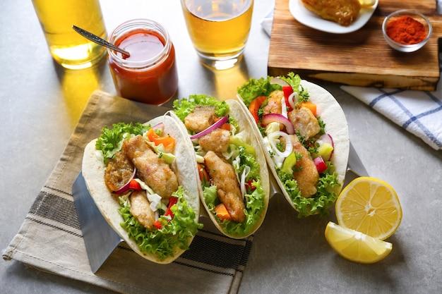 테이블에 맛있는 생선 타코와 함께 서십시오.