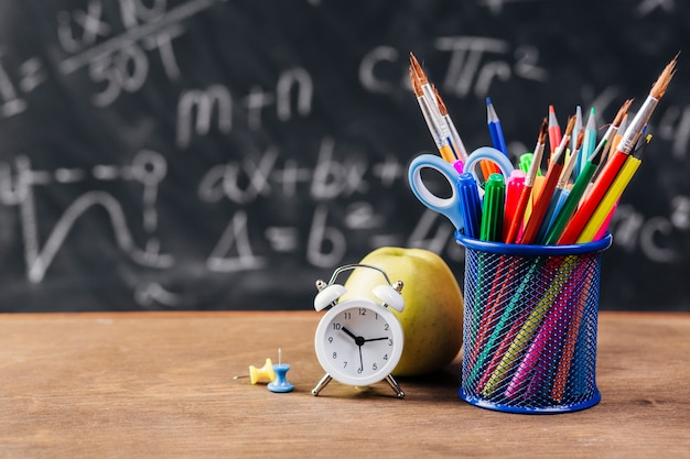 Stand with drawing tools and alarm clock on chalkboard background