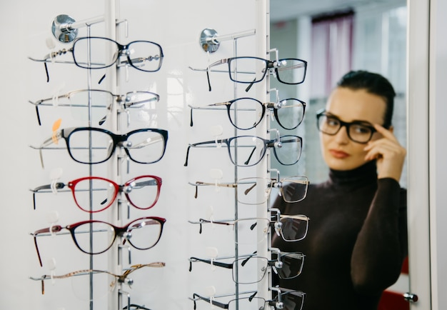 Stand with glasses in an optician's store with a beautiful girl