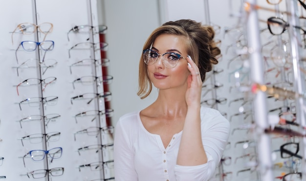 안경을 쓰고 서십시오. 시력 교정. 안경을 쓴 소녀. 안경을 교정하는 여자의 초상화입니다.