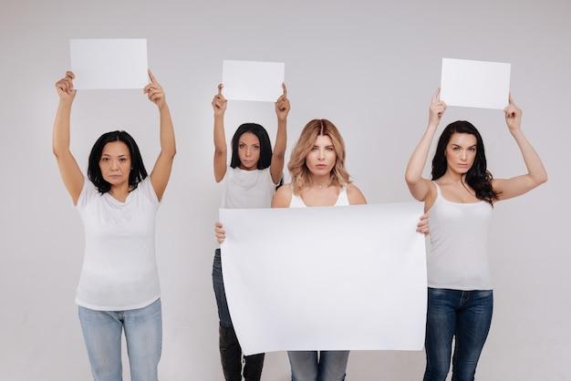 私たちと一緒に立ってください。社会的な抗議のために立ち上がり、空白のプラカードを持っている優雅で見事な現代の女性