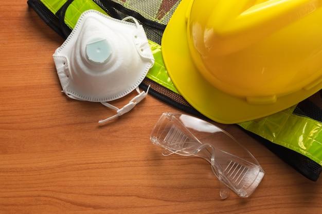 Standard construction safety glasses mask helmet reflective shirt on wooden plank.