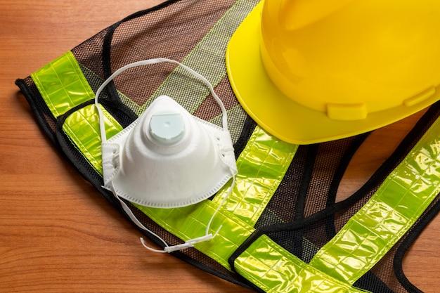 Standard construction safety mask glasses helmet reflective shirt on wooden plank.