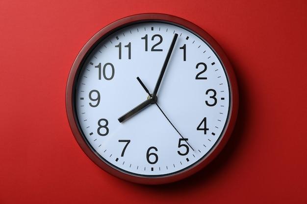 Стандартные красные домашние часы на красном фоне