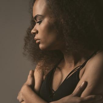 Стоящая афроамериканская девушка, одетая в черный топ