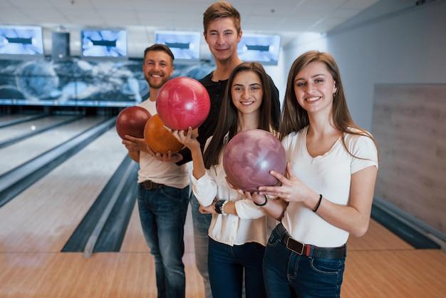 In piedi contro l'area di gioco. i giovani amici allegri si divertono al bowling durante i fine settimana