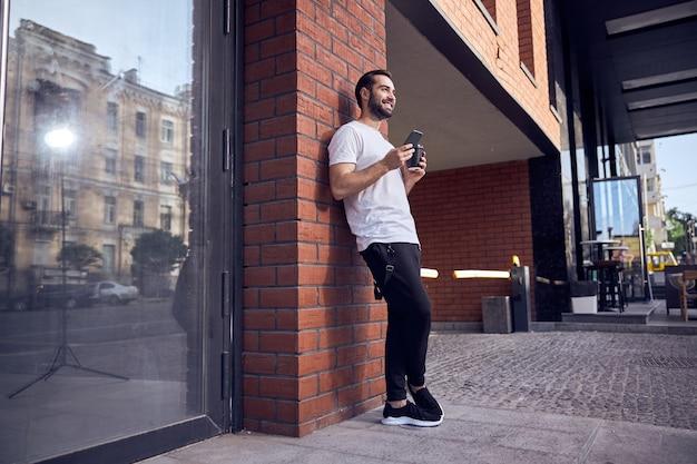 스마트 폰 및 커피와 함께 벽 근처에 서 있고 재미있는 남자
