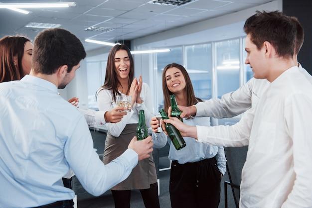 Стоя и выбивая бутылки и бокалы. в офисе. молодые люди празднуют свой успех