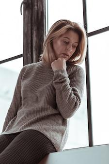 立って待っています。窓の近くに立ち、仕事から夫を待つ金髪の女性