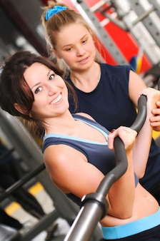 Standing attractive smiling brunette girl looking at camera and training with barbell in hands under the supervision of trainer woman