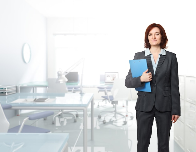 Стоящая кавказская женщина в современном офисе