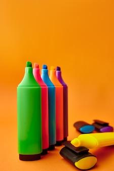 Постоянный красочный постоянный крупный план маркеров на оранжевой стене. канцелярские товары, школьные или образовательные принадлежности, инструменты для письма и рисования