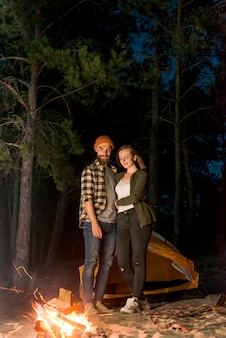 Standing couple looking at the campfire