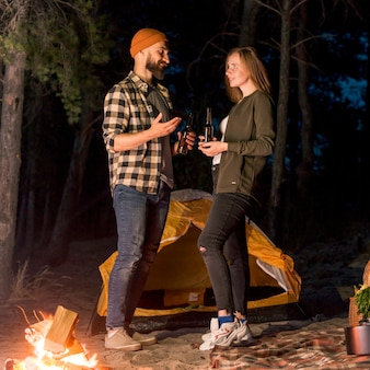 Standing couple talking by camping tent