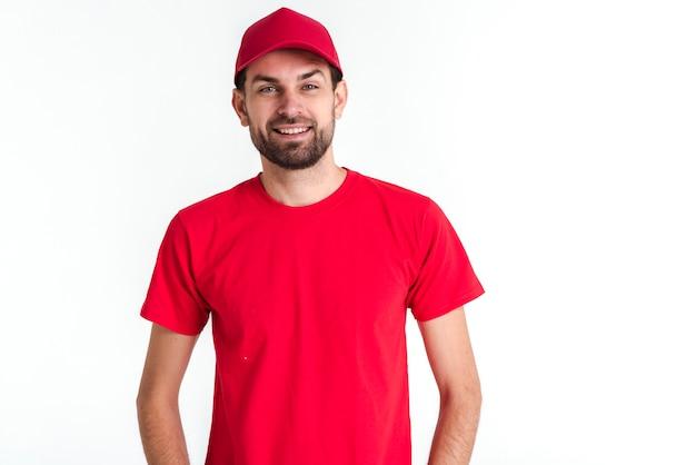 赤い制服を着た立っている宅配便の男