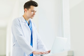 Standing doctor with laptop