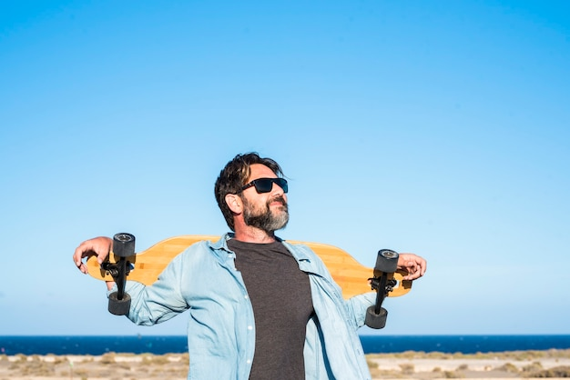 Standing free bearded handsome adult man with long board skate enjoying freedom and healthy lifestyle - blue ocean and sky in background - concept of active people