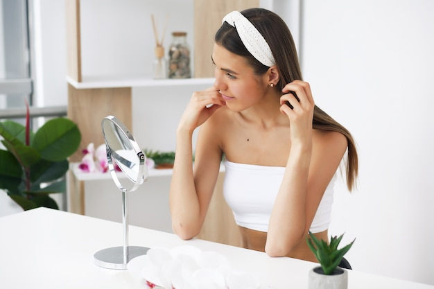 Standing in front of a mirror, enjoying beauty treatments for herself