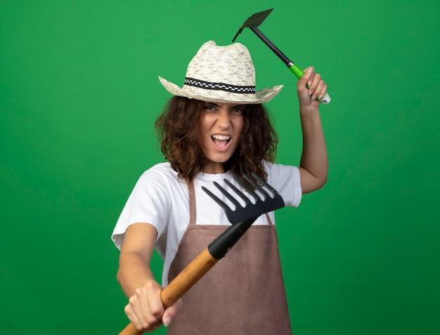 괭이 갈퀴와 갈퀴를 들고 원예 모자를 쓰고 제복을 입은 젊은 여성 정원사 포즈 싸움에 서