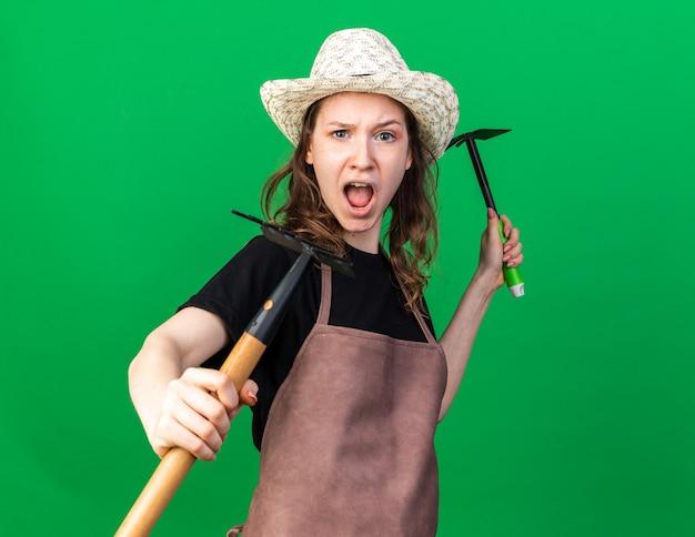 戦いのポーズで立っている若い女性の庭師は、くわ熊手で熊手を保持している園芸帽子をかぶっています