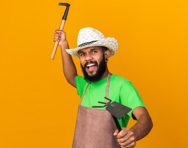 괭이 갈퀴와 갈퀴를 들고 원예 모자를 쓰고 싸우는 포즈 젊은 정원사 아프리카계 미국인 남자에 서
