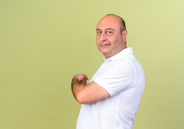 Стоя в профиль и глядя в камеру, зрелый мужчина указывает на спину, изолированную на оливково-зеленом с копией пространства