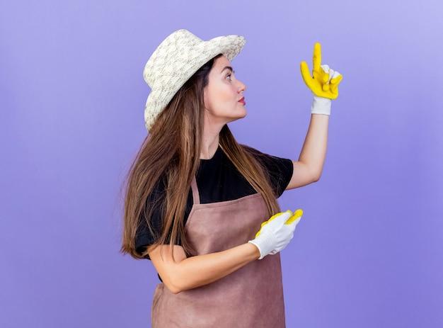 Стоя в профиль, красивая девушка-садовник в униформе в садовой шляпе и перчатках указывает на разные стороны, изолированные на синем