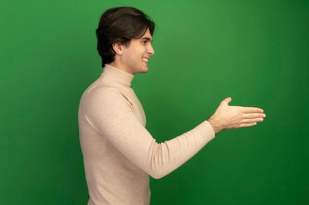 녹색 벽에 고립 된 앞에 손을 들고 프로필보기 웃는 젊은 잘 생긴 남자에 서