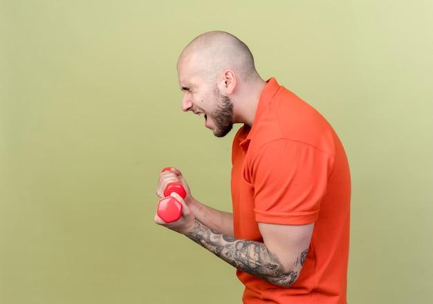 Стоя в профиль, напряженный молодой спортивный мужчина тренируется с гантелями, изолированными на оливково-зеленой стене