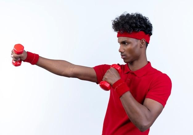 Стоя в профиль, молодой афро-американский спортивный мужчина с повязкой на голову и браслет с гантелями, изолированными на белом