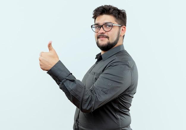 Стоя в профиль вид молодой бизнесмен в очках его большой палец вверх, изолированные на белом