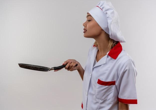 プロフィールビューに立ってコピースペースで彼女の手でフライパンを見ているシェフの制服を着た若い料理人の女性